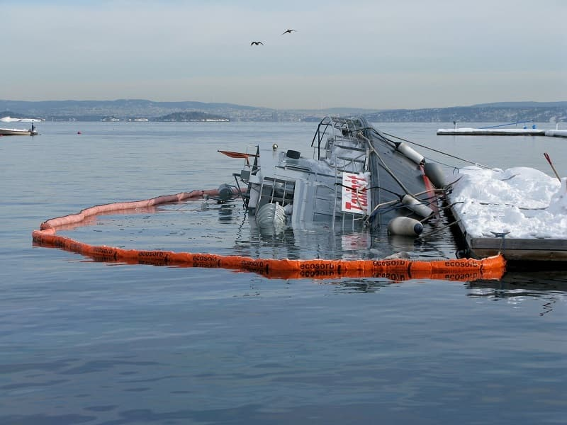 Oil spill. Sunken yacht in ice